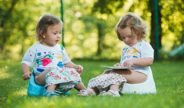 The two little baby girls two-year old sitting on pottys on green grass of lawn, Image: 294530295, License: Royalty-free, Restrictions: , Model Release: yes, Credit line: Profimedia, Alamy